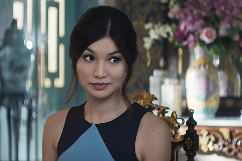 Gemma Chan wears her hair up with a few tendrils escaping. She sits with a vase and flowers on an opulent table behind her.
