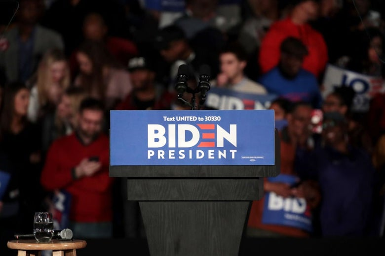 An empty lectern decorated with a Biden logo against the backdrop of supporters at a rally.