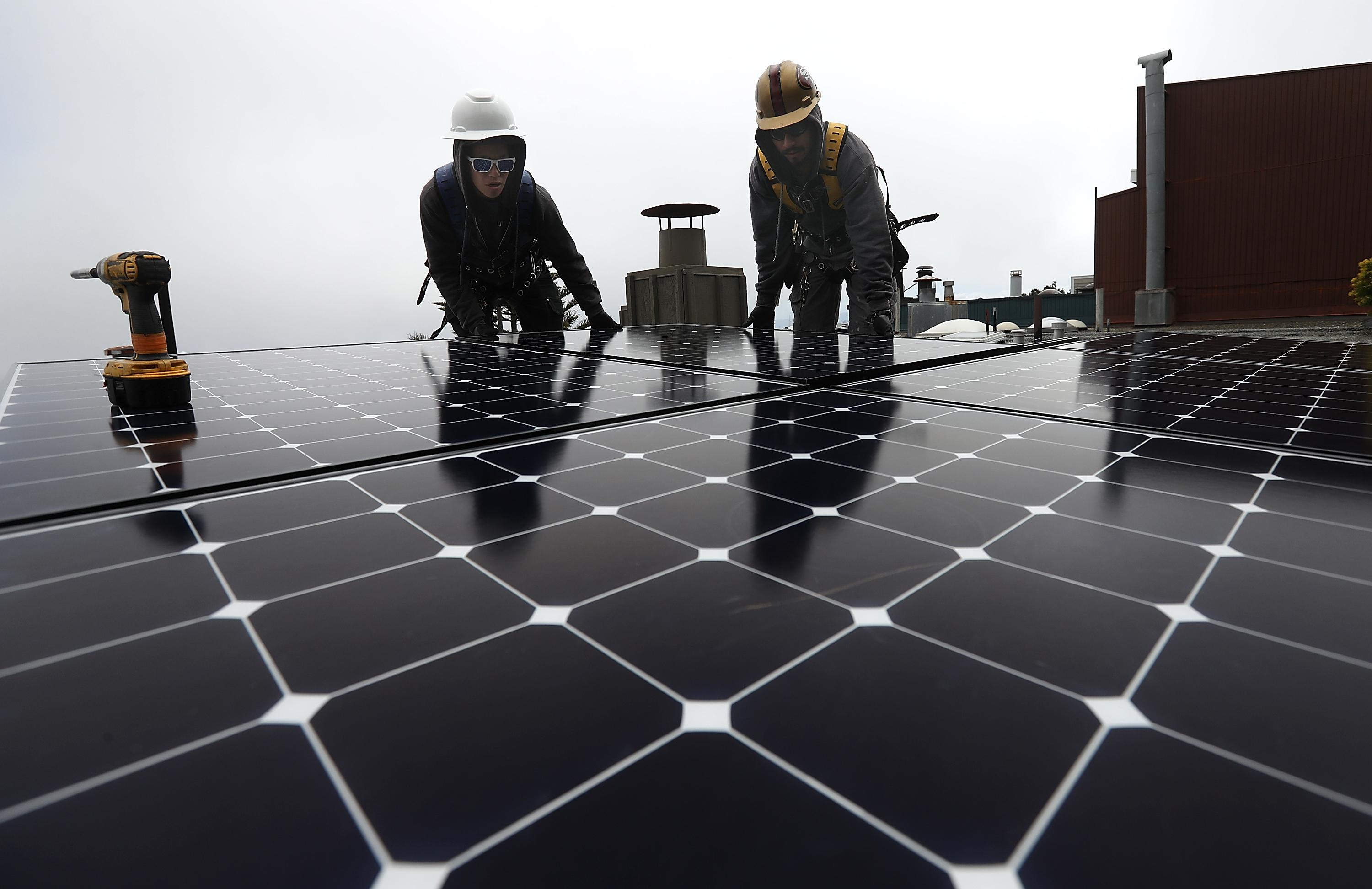 Workers of Luminalt, a solar panel company, install solar panels on the roof of a home on May 9, 2018 in San Francisco, California.