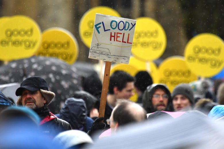 "A crowd of protesters holding signs that say ""Good energy"" and one that says ""Floody Hell"""