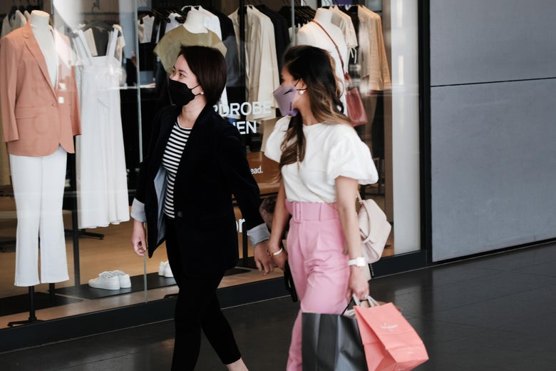 Two women in masks walk through a mall with shopping bags.
