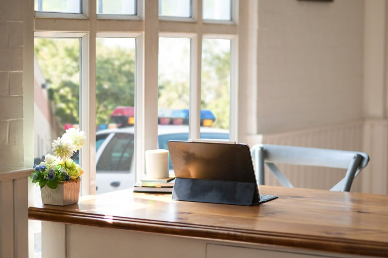 A laptop with a stand sits on a table. The table also features a small flowerpot and a mug on top of two books. The table is near a sunlit window and stands in front of a chair.