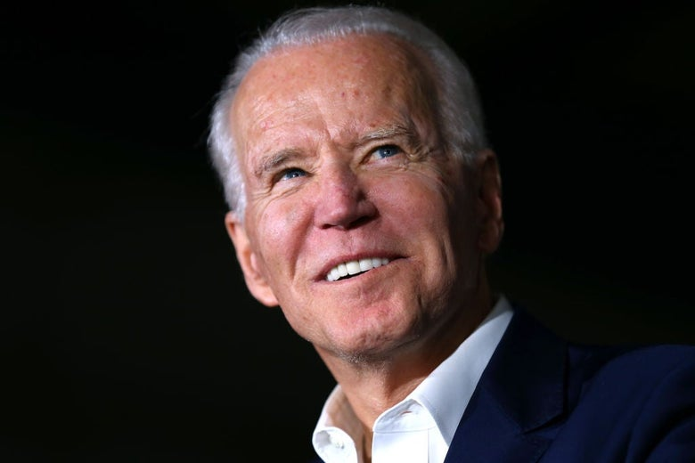 Biden, wearing a blue coat and open-collar white shirt, looks up and to his left against a black backdrop.