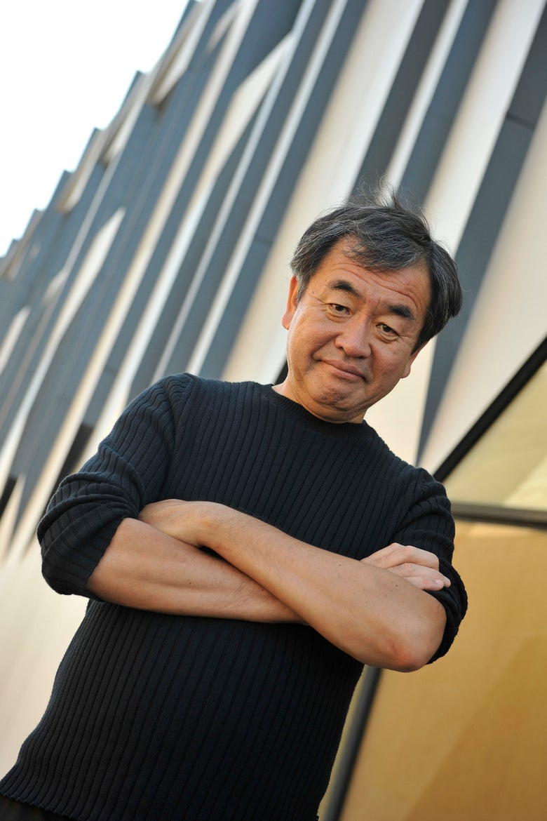A portrait of Kengo Kuma, standing with his arms crossed and wearing a black shirt.