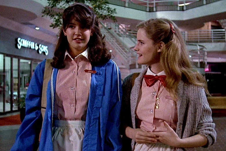 Two teen girls wearing red and white striped restaurant uniforms talking in a mall
