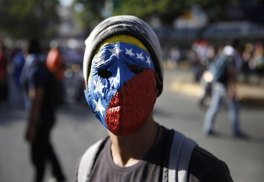 A demonstrator wearing a mask depicting the national flag takes part in a protest against President Nicolas Maduro's government in Caracas February 16, 2014.