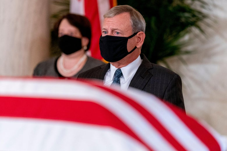 John Roberts stands in front of a flag-draped casket wearing a mask. Elena Kagan, also masked, can be seen in the background.