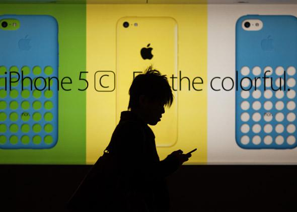 A man uses his phone as he walks past an Apple Store on Dec. 25, 2013.