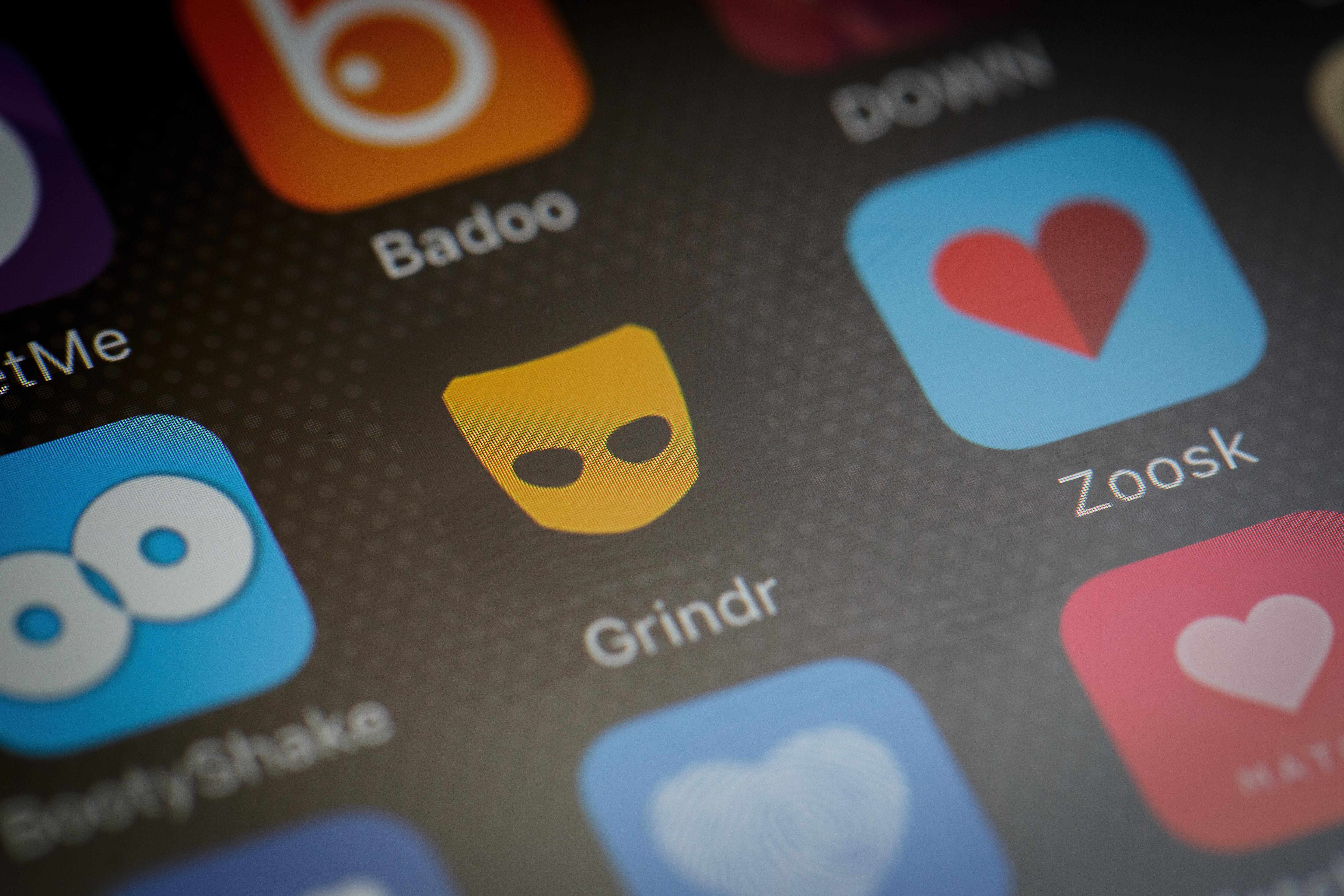 The 'Grindr' app logo is seen amongst other dating apps on a mobile phone screen.