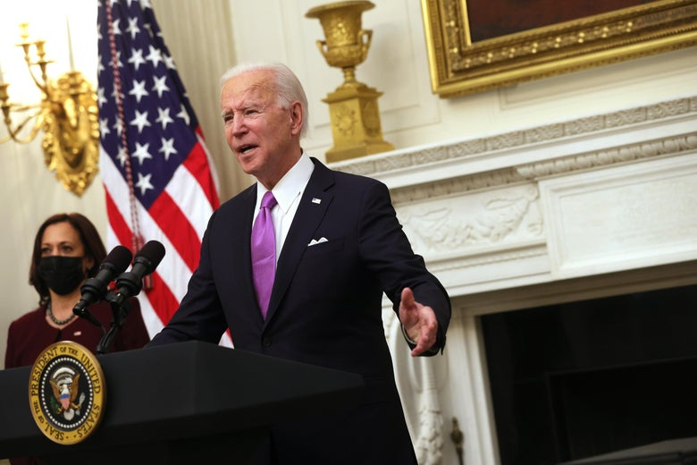 Biden raises his arms as he speaks at a podium in the State Dining Room of the White House. Vice President Kamala Harris looks on behind him.