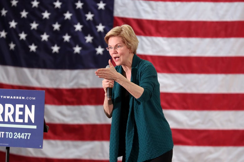 Warren, holding a microphone, speaks against an American flag backdrop.