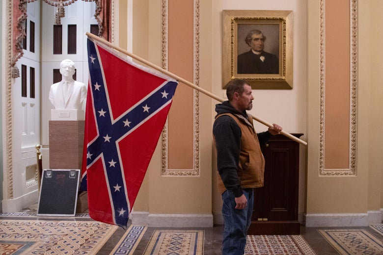 A man holding a Confederate flag stands in front of a portrait of an old member of Congress in a hallway of the Capitol.