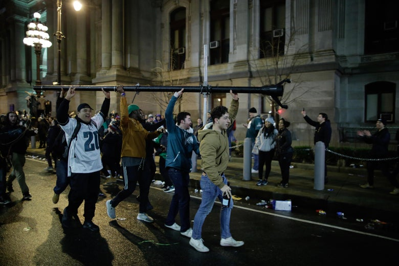 People carry a broken pole while celebrating the Philadelphia Eagles victory in Super Bowl LII.