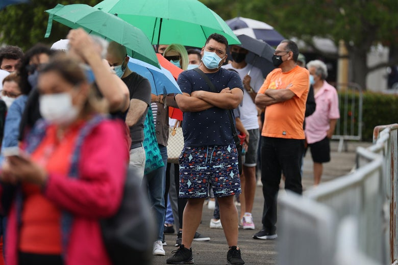 Amid a line of people holding umbrellas while waiting, a man in a mask stands with his arms crossed.