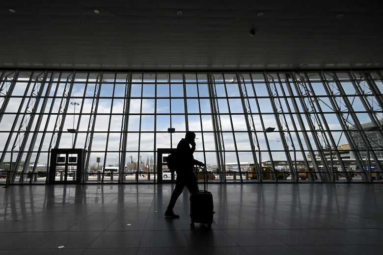 A man with a rolling luggage walks through an airport terminal.
