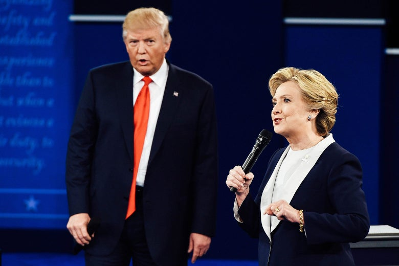 Hillary Clinton holds a microphone onstage with Donald Trump looking on.