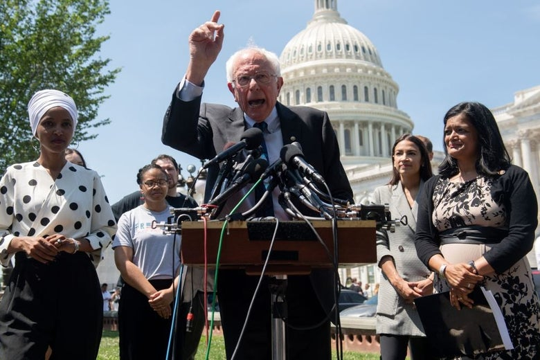 Sanders gestures in fiery fashion while speaking at a lectern with the Capitol dome behind him.