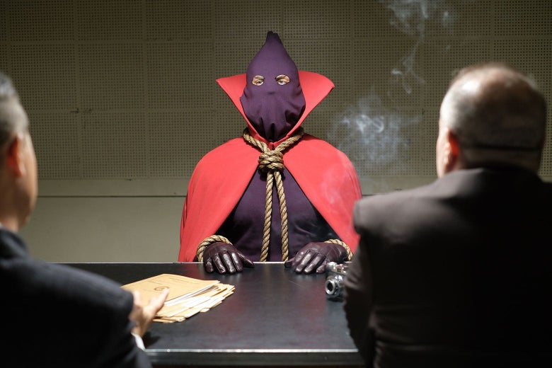 Hooded Justice sits at a table in an interrogation room in this still from HBO's Watchmen.