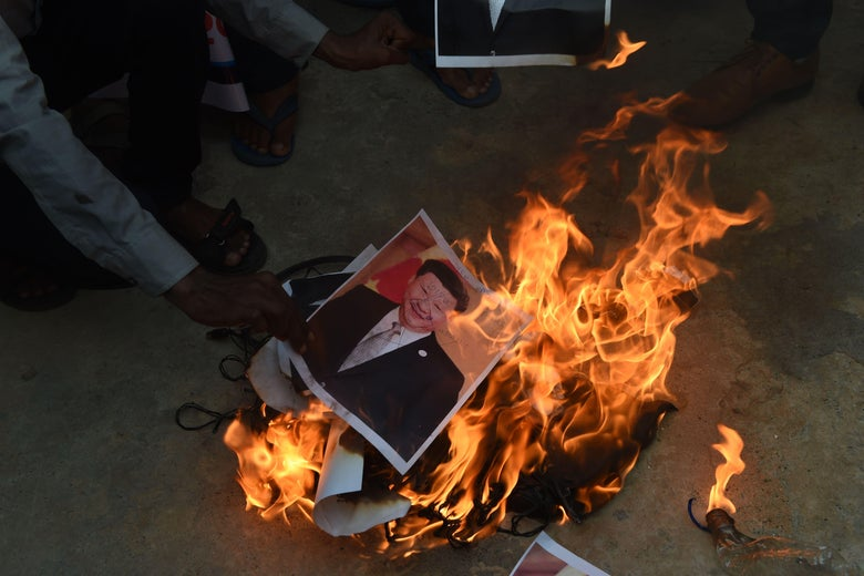 A hand puts photo of Xi Jinping into a ground fire.