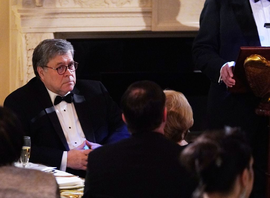 Barr is pictured seated at a table and wearing a tuxedo.
