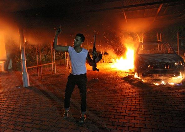 This file photo taken on September 11, 2012 shows an armed man waving his rifle as buildings and cars are engulfed in flames after being set on fire inside the US consulate compound in Benghazi.