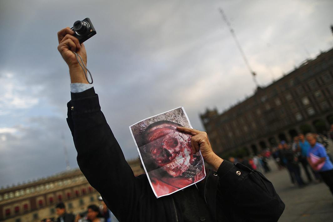 A demonstrator holds a picture of an unidentified dead person during a protest in support of the missing Ayotzinapa students in Mexico City's Zocalo Square on Nov. 8
