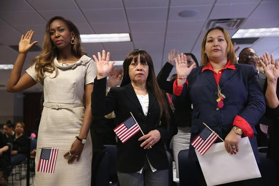 Immaculee Ilibagiza, from Rwanda, (L) and other immigrants take the oath of American citizenship at a naturalization ceremony on April 17, 2013 in New York City. Fifty immigrants from 15 countries became American citizens at the ceremony held by the U.S. Citizenship and Immigration Services (USCIS).