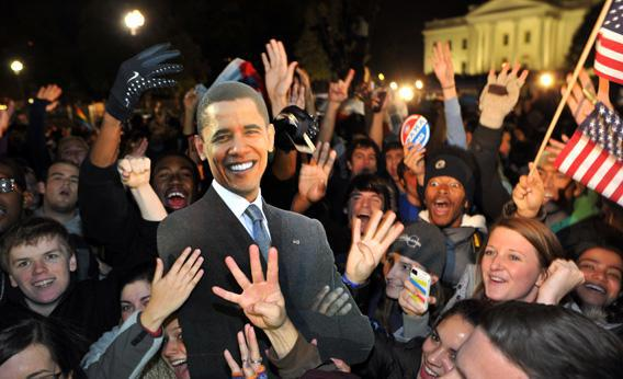 People celebrate in front of the White House with a cardboard cutout of the President Obama.