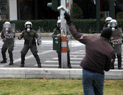 An Athens anarchist throws a stone at riot police. Click image to expand.