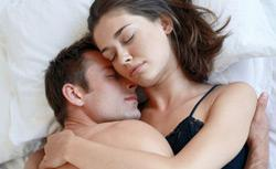 Couple cuddling in bed. Click image to expand.