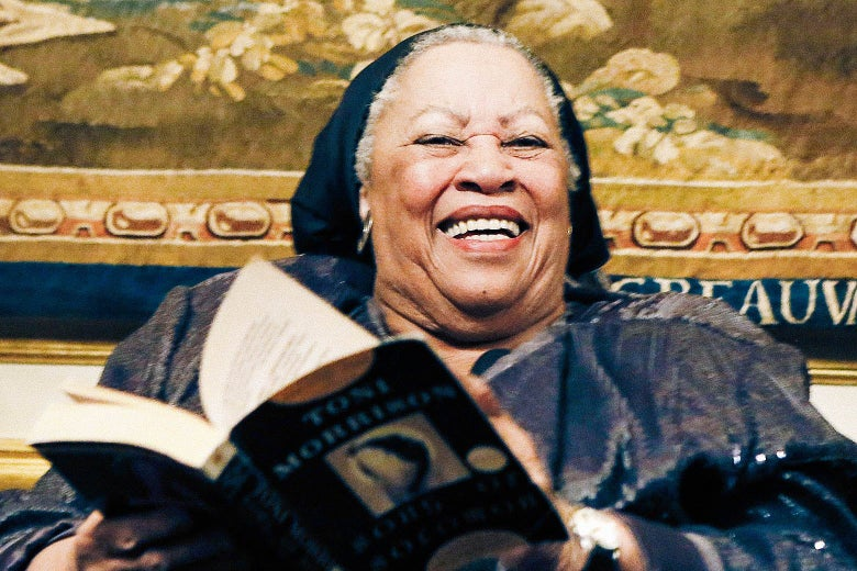 Toni Morrison smiling at a reception while turning the page of a book.