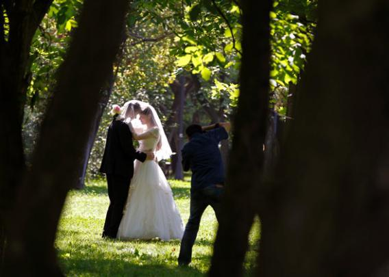 A photographer takes wedding pictures of a couple at a park, August 7, 2013.