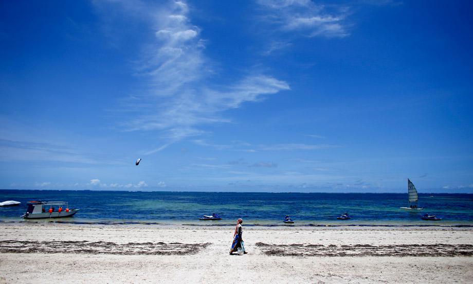 A woman walks by the beach of Kenya's coastal city of Mombasa March 6, 2013.