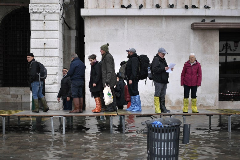 People walk across a footbridge in a flooded street in Venice.