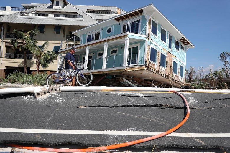 A man walks a bike in front of a blue house that has been pushed up against another house. In the foreground, the road is cracked and distorted.