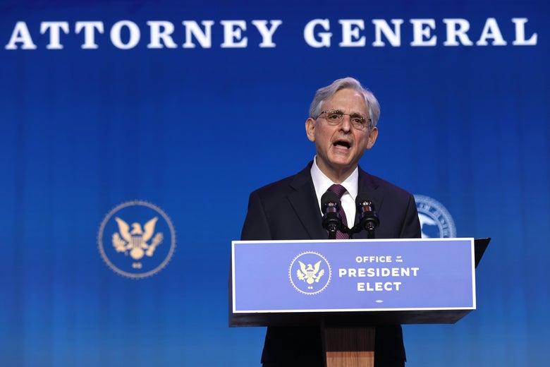 Garland speaks at a podium labeled Office of the President Elect, with the words Attorney General on a backdrop partially cut off behind him