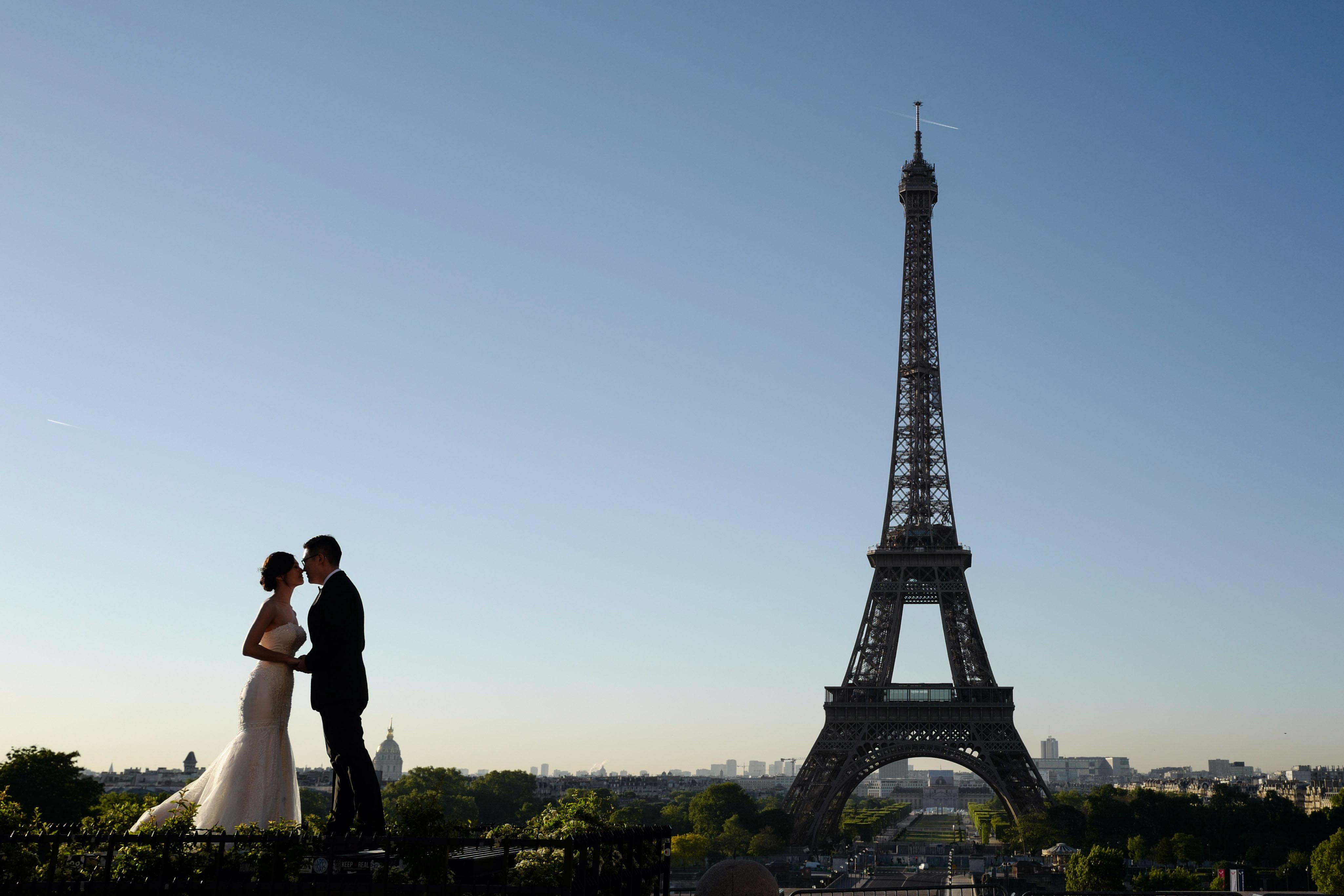 A married couple poses in front of the Eiffel tower at sunrise on Trocadero square.