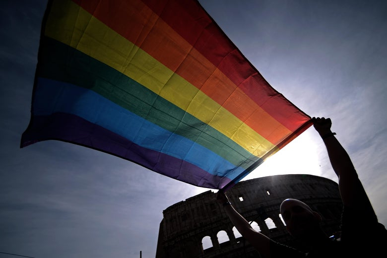 A demonstrator waves a rainbow flag during a Gay Pride Parade at the Colosseum in Rome.