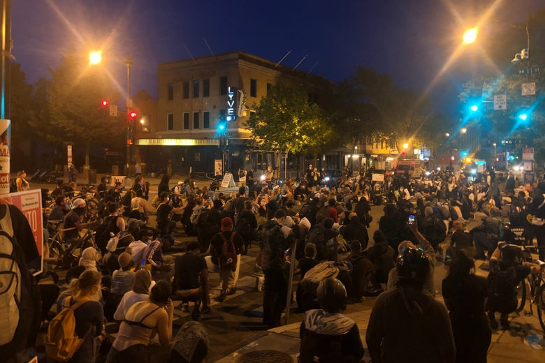 A large crowd of protestors kneel at an intersection in D.C.