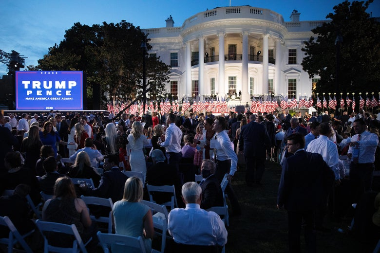 The south lawn of the White House, filled with people overshadowed by a giant Trump Pence sign.