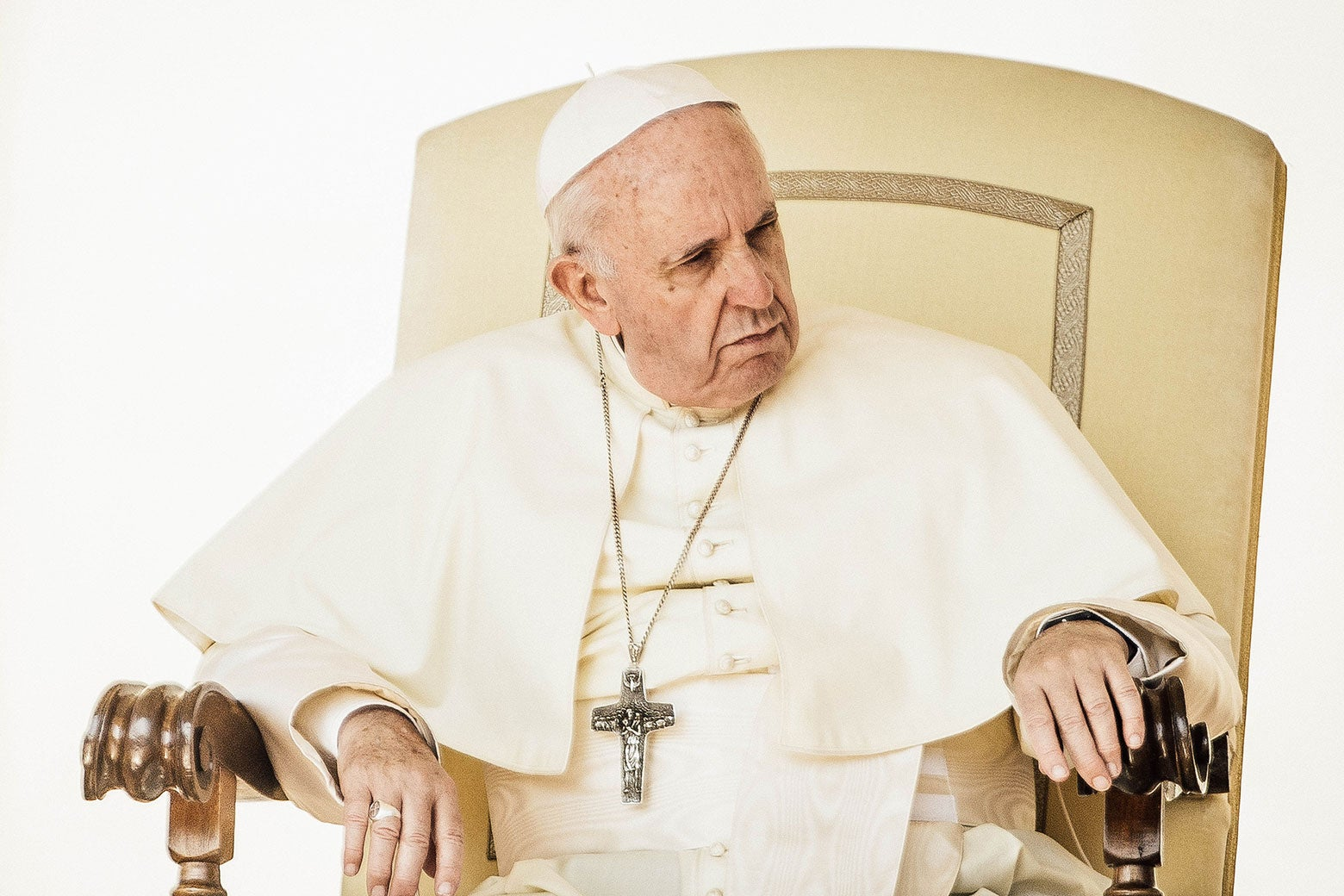 Pope Francis sits in an ornate chair.