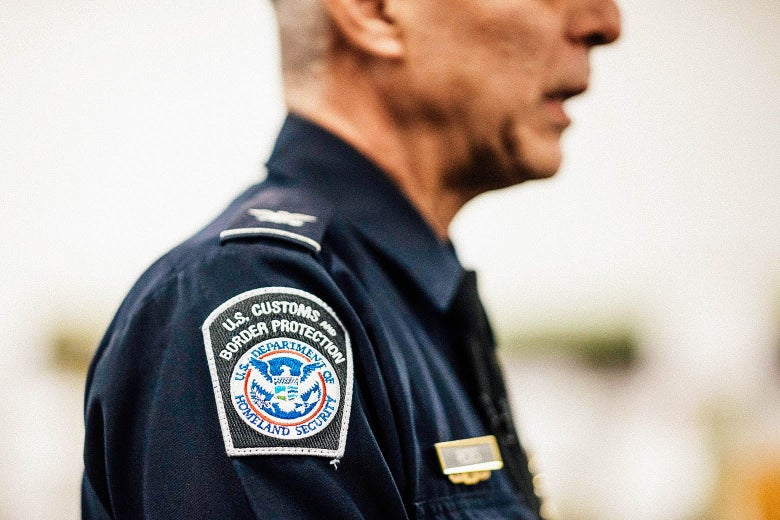 A man in a U.S. Customs and Border Protection uniform is seen from the side, with a focus on the agency's logo embroidered on his shoulder.