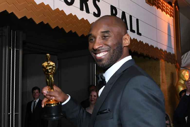 Kobe Bryant enters the Governor's Ball, holding his Academy Award.