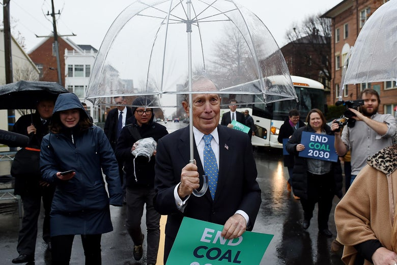 "Michael Bloomberg walks with other people on a city street on a rainy day, carrying an umbrella and a sign that says ""End Coal 2030."""
