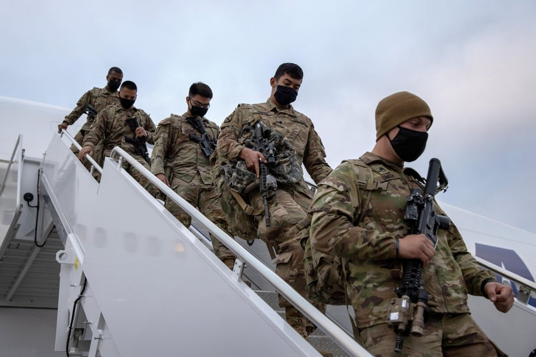 Uniformed troops walking down the stairway from a plane.
