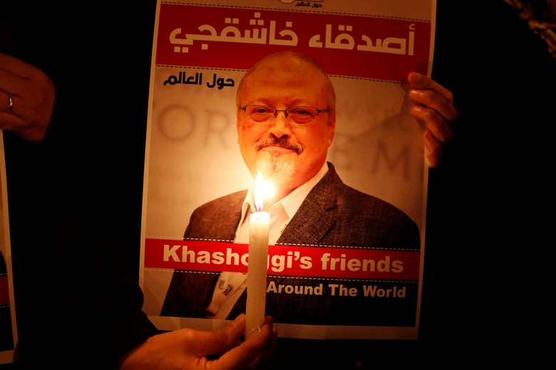 A demonstrator holds a candle in front of a poster with a picture of Saudi journalist Jamal Khashoggi.