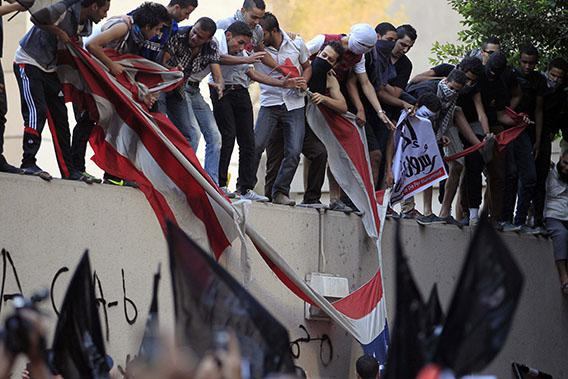Protesters destroy an American flag pulled down from the U.S. embassy in Cairo September 11, 2012.