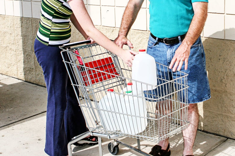 Two people loading a shopping cart with jugs of water.