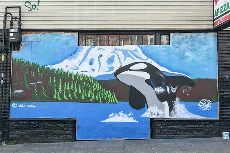 A mural beneath a sign for pizza shows an orca leaping out of a mountainside lake.