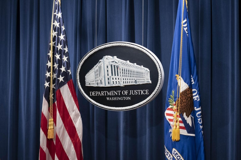 A sign for the Department of Justice between two flags